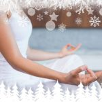 31858793 - peaceful woman in white sitting in lotus pose  against fir tree forest and snowflakes